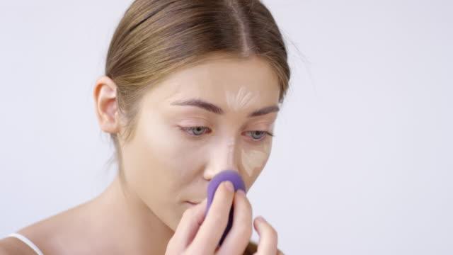 vídeos de stock e filmes b-roll de close up of woman blending concealer - esponja