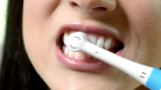 vídeos de stock e filmes b-roll de close up of woman brushing teeth with electric toothbrush - escovar