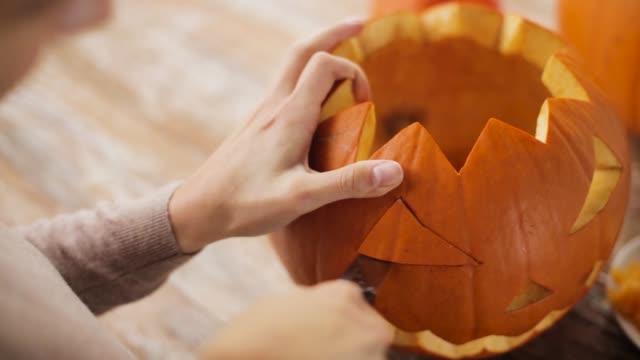 close up of woman carving halloween pumpkin - pumpkin стоковые видео и кадры b-roll