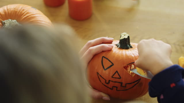 Close up of woman carving pumpkin for Halloween