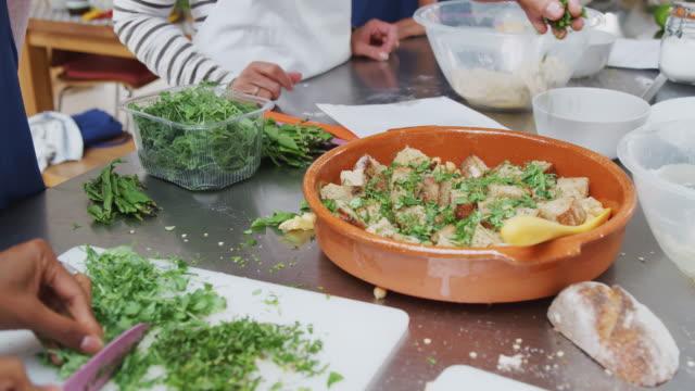 特寫婦女切碎和添加新鮮的草藥到廚房烹飪類的菜肴 - 食物和飲品 個影片檔及 b 捲影像
