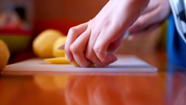 Close up of woman cutting potato Young woman in the kitchen preparing a dinner prepared potato stock videos & royalty-free footage