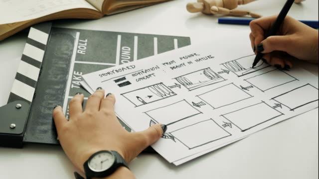 nahaufnahme von frau direktor ist storyboard der kurzfilm neben clapper board-movie schaffensprozess skizzieren - storytelling videos stock-videos und b-roll-filmmaterial