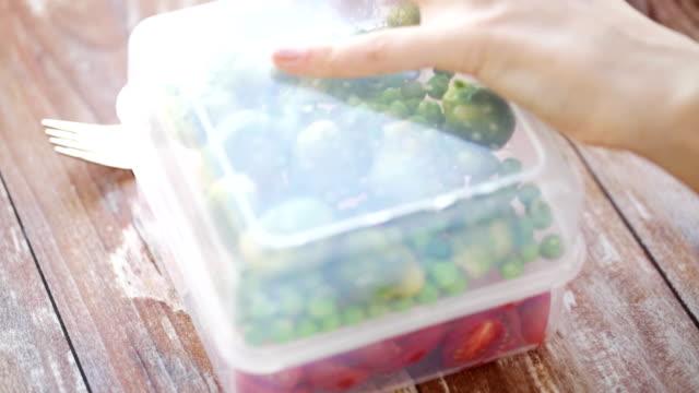 コンテナーから野菜を食べる女のクローズ アップ - ローフード点の映像素材/bロール