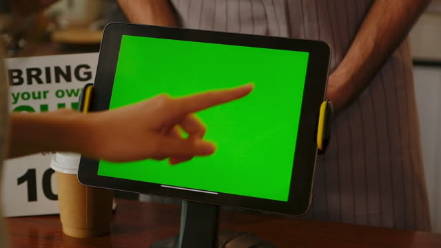 Close up of woman hand touching digital tablet with blank green screen at coffee shop cafe counter, Digital tablet screen background, template for ordering coffee menu, slow motion