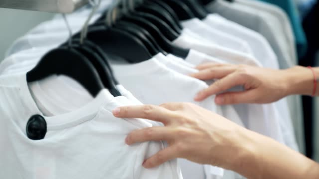 close up of woman hands, look through clothes on rack, buyer chooses white t-shirt - maglietta video stock e b–roll