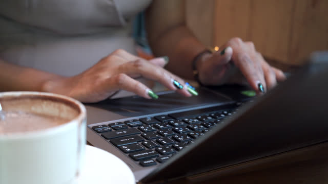 Close up of Woman hands using laptop computer in cafe
