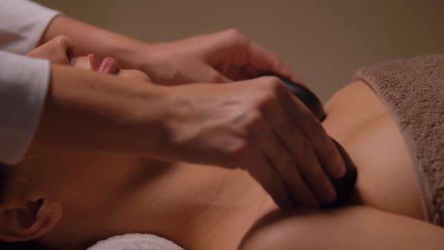 close up of woman having hot stone massage at spa wellness, beauty and relaxation concept - close up of young woman having hot stone massage at spa spa treatment stock videos & royalty-free footage