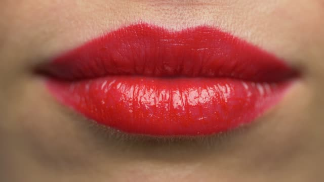 close up of woman lips with red lipstick making kissing beauty, make up and mouth expression concept - close up of woman lips with red lipstick making kissing red lipstick stock videos & royalty-free footage