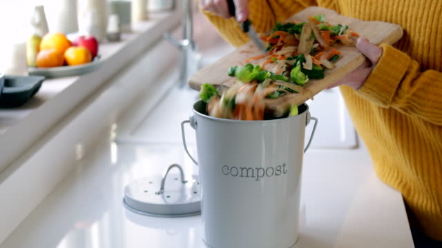 Close Up Of Woman Making Compost From Vegetable Leftovers In Kitchen Close Up Of Woman Making Compost From Vegetable Leftovers In Kitchen leftovers stock videos & royalty-free footage