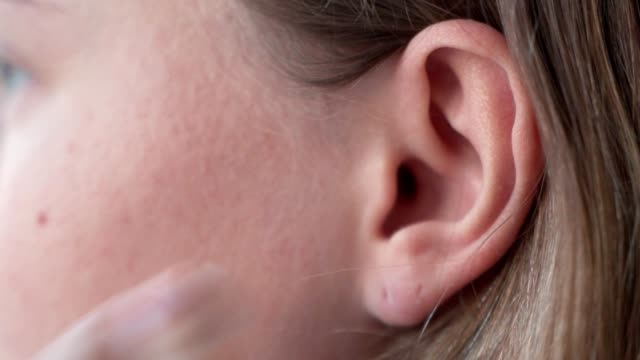 Close up of woman putting earphones in his ear to listen to music and starts dancing to the beat of the music