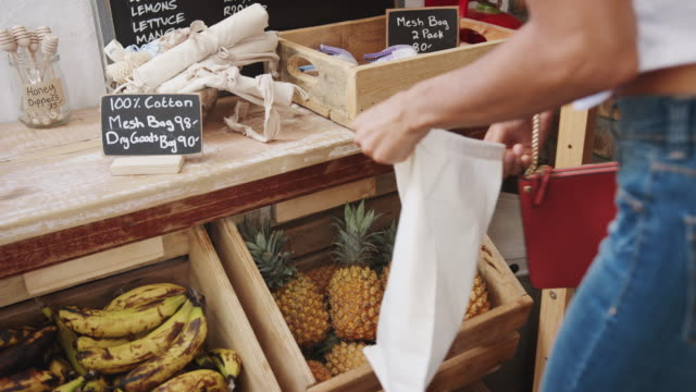 close up of woman putting pineapple into reusable cotton bag in plastic free grocery store - sustainability video stock e b–roll