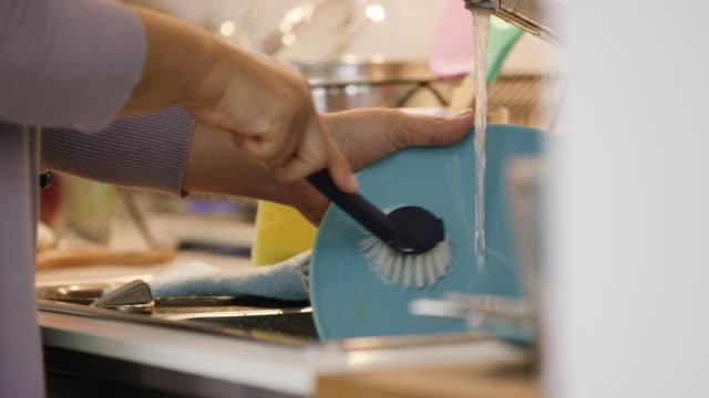 vídeos de stock e filmes b-roll de close up of woman scrubbing dirty dishes - economia circular