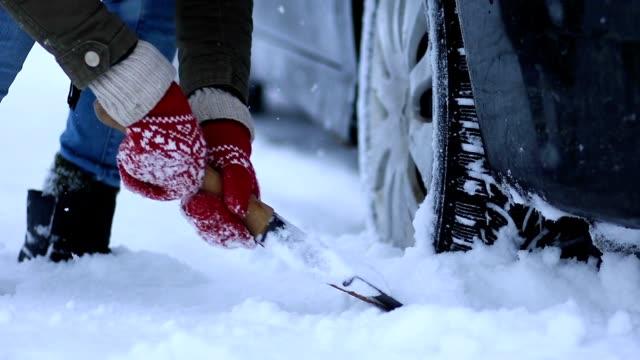 närbild av kvinna skotta snö från bilen - skyffel bildbanksvideor och videomaterial från bakom kulisserna