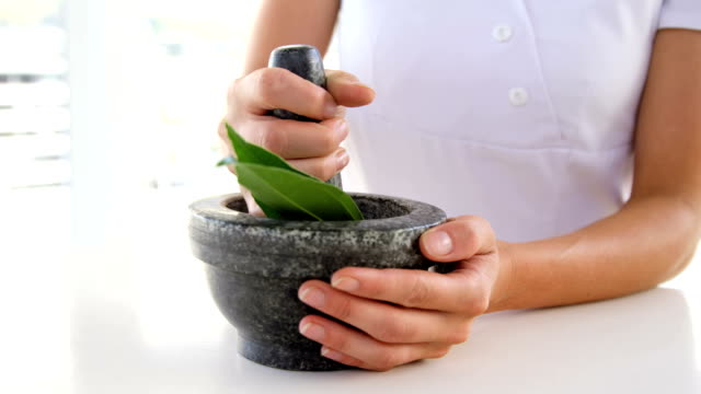 Close up of woman therapist preparing a mixture Close up of woman therapist preparing a mixture with a pestle mortar and pestle stock videos & royalty-free footage