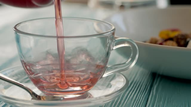 Close up of woman waiter pouring hot herbal carcade tea in transparent glass cup in slow motion. Healthy breakfast in restaurant with granola on background video