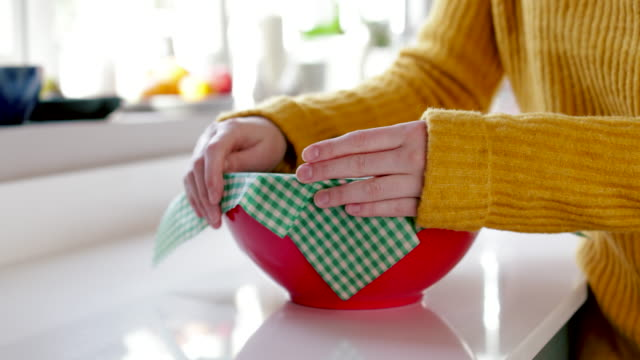 Close Up Of Woman Wrapping Food Bowl In Reusable Environmentally Friendly Beeswax Wrap Close Up Of Woman Wrapping Food Bowl In Reusable Environmentally Friendly Beeswax Wrap leftovers stock videos & royalty-free footage