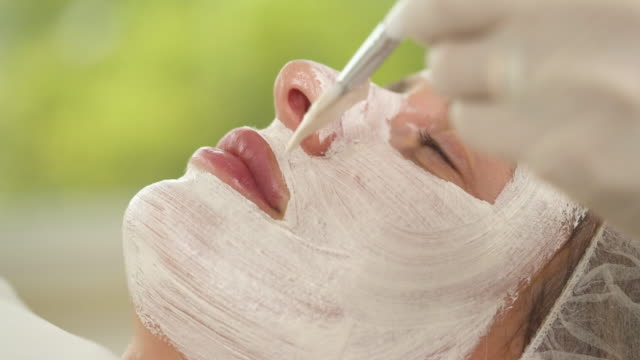 a close up of woman's face covered with white mask. a hand with a brush applies more mask substance on the face - prendersi cura del corpo video stock e b–roll