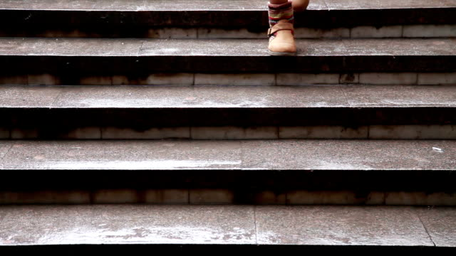 Close up of woman's feet walking down the marble stairs video