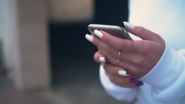 nahaufnahme der hand der frau mit einem mobiltelefon. das mädchen nutzt ein smartphone für online-shopping. - fingernagel stock-videos und b-roll-filmmaterial