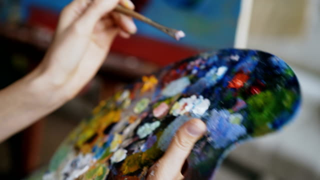close up of woman's hand mix paints with brush in palette in art-class - cavalletto attrezzatura per arti e mestieri video stock e b–roll