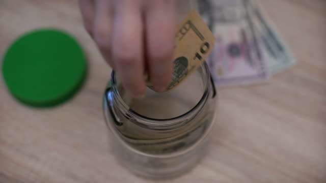 close up of woman's hand putting money usa dollar into glass jar close up of woman's hand putting money usa dollar into glass jar jar stock videos & royalty-free footage