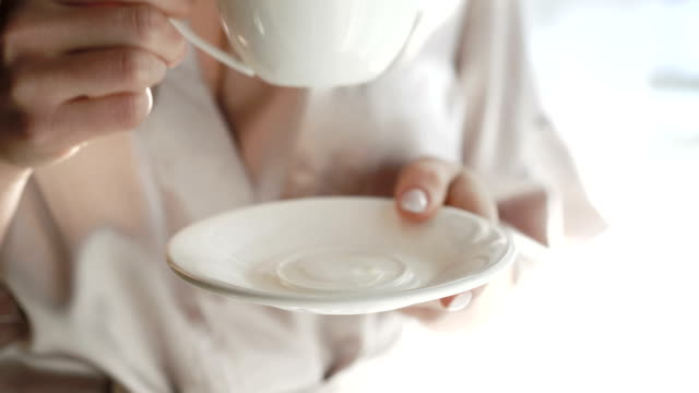 close up of woman's hands holding white saucer and drinking fullhd - piattino video stock e b–roll