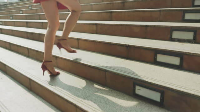 vídeos de stock e filmes b-roll de close up of woman's legs stepping up on stairway in city - stock video - saia