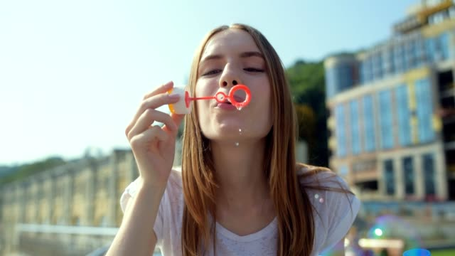 Close up of wonderful girl blowing bubbles outside video