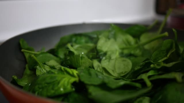 close up of wooden spoon stirring wilted spinach in a heated pan - jedzenie wegetariańskie filmów i materiałów b-roll