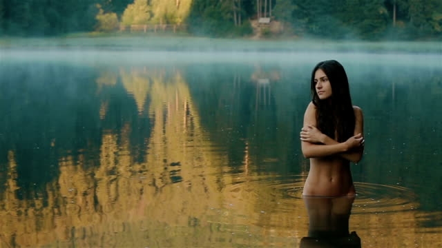 Close up of young and beautiful seductive girl mermaid with no make up and  long dark hair softly touching her skin with view of mountain Synevir lake on background. Carpathian mountains Close up of young and beautiful seductive girl mermaid with no make up and  long dark hair softly touching her skin with view of mountain Synevir lake on background. Carpathian mountains. seductive women stock videos & royalty-free footage