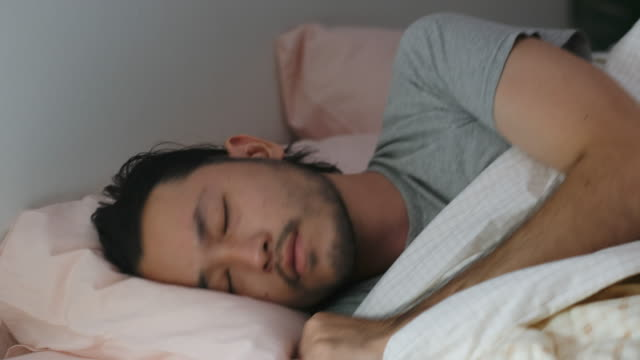 Close up of young asian man bad sleep, insomnia lying on bed