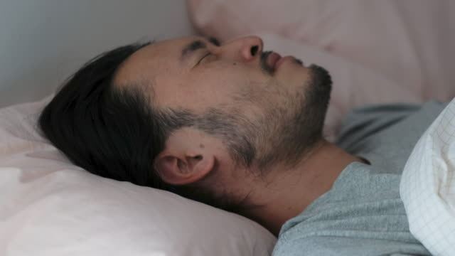 vídeos de stock e filmes b-roll de close up of young asian man bad sleep, insomnia lying on bed - dormir