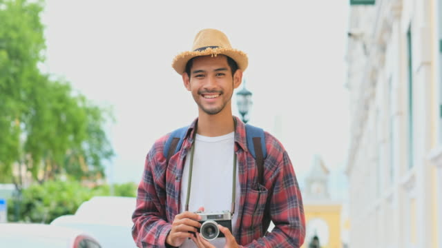 Close up of young asian man tourist holding camera for photographing while travel along the city street smiling and looking at camera, Teenage backpacker on journey in summer vacation in asia