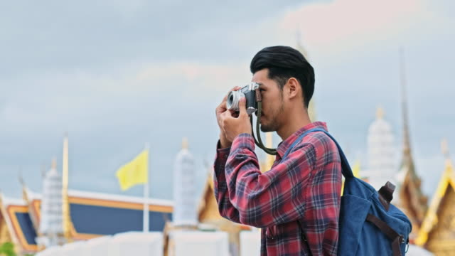 Close up of young asian man tourist holding camera for photographing while travel along the city street, Teenage backpacker on journey in summer vacation in asia