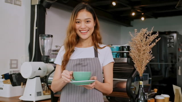 Close up of young asian woman barista holding coffee cup, smiling and looking at camera while standing at counter in coffee shop cafe, slow motion