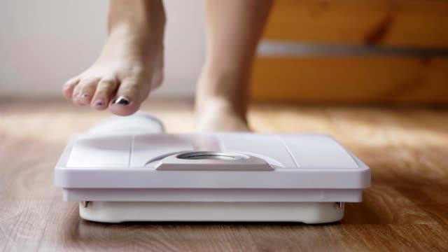 close up of young asian woman checking body weight on weighing scale in the living room at home. - fare un passo video stock e b–roll