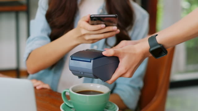 Close up of  young asian woman customer hand making contactless payment through smart phone with waitress hand holding credit card reading machine to service costumer at table in cafe, slow motion Close up of  young asian woman customer hand making contactless payment through smart phone with waitress hand holding credit card reading machine to service costumer at table in cafe, slow motion tapping stock videos & royalty-free footage