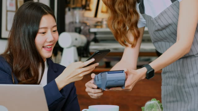 Close up of  young asian woman customer making conractless payment through smart phone with waitress hand holding credit card reading machine to service costumer at table in cafe Close up of  young asian woman customer making contactless payment through smart phone with waitress hand holding credit card reading machine to service costumer at table in cafe tapping stock videos & royalty-free footage