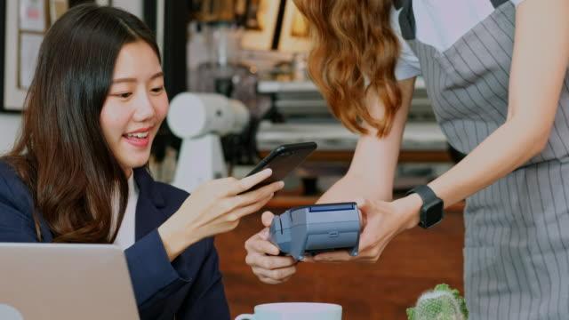 primo tempo della giovane cliente asiatica che effettua pagamenti senza problemi tramite smartphone con la mano della cameriera che tiene in mano la macchina per la lettura della carta di credito per il cliente di servizio a tavola al bar - picchiettare video stock e b–roll