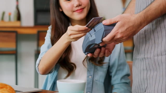 Close up of young asian woman customer making contactless payment through credit card with waiter hand holding credit card reading machine to service costumer at table in cafe, slow motion Close up of young asian woman customer making contactless payment through credit card with waiter hand holding credit card reading machine to service costumer at table in cafe, slow motion contactless payment stock videos & royalty-free footage