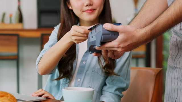 close up of young asian woman customer making contactless payment through credit card with waiter hand holding credit card reading machine to service costumer at table in cafe, slow motion - picchiettare video stock e b–roll