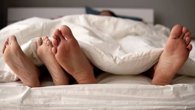 close up of young beautiful and loving couple play and dance their feet under blanket while wake up in bed in morning. white bed sheets - dito del piede video stock e b–roll