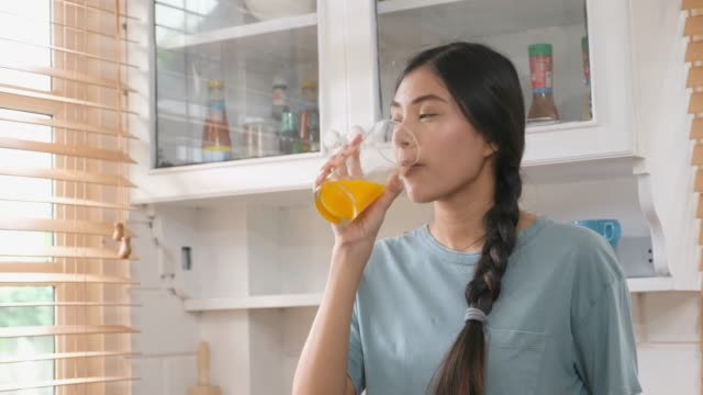 Close up of young beautiful asian woman drinking orange juice in kitchen, Healthy lifestyles