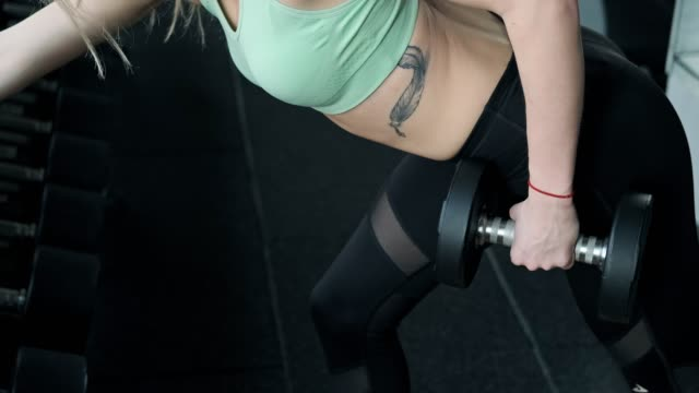Close up of young beautiful woman doing sport exercise with dumbbells