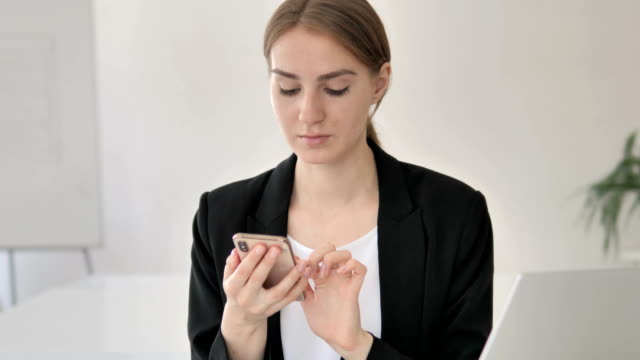 Close up of Young Businesswoman in Shock Using Smartphone