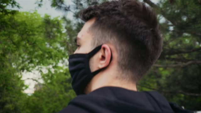 close up of young caucasian tourist man wearing protective face mask walking in urban park during coronavirus pandemic - viaggiare zaino in spalla video stock e b–roll