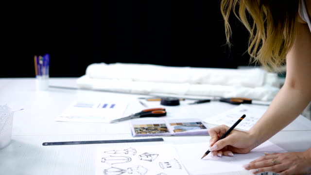 close up of young fair-haired woman standing bending over working table in tailoring studio and drawing future dresses. clothes designer is creating new fashion collection doing sketches with pencil - designers video stock e b–roll
