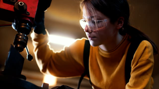 Close up of young female welder There are two woman and one man, they are in their shop, working together. metal worker stock videos & royalty-free footage