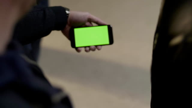 Close up of young male hands holding modern smartphone with green touch screen. Man's hand shows mobile smartphone with green screen to his friend video